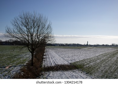 Lonley tree in a winter landscape with a church near Rietmolen, the Netherlands