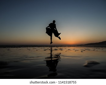lonley woman wide trousers as silhouette at a sunset beach in morocco