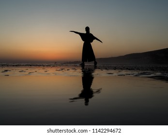 lonley woman wide trousers as silhouette making different postures at a sunset beach in morocco