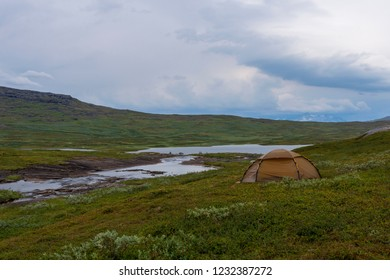 Lonly tent high up on a mountain plateau near a river with a cloudy sky in background, picture from Norway.