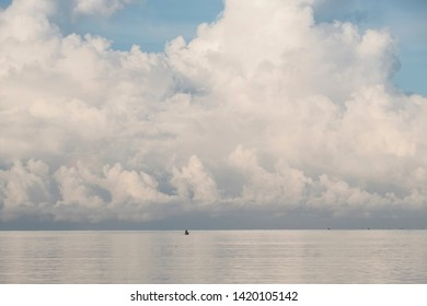 lonsome fishermen in traditionel dugout canoe in the wide ocean of south with dramatic clouds above pacific