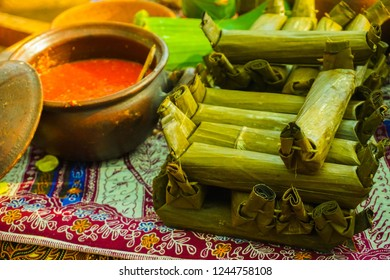 lontong or boiled rice wrapped with banana leaf and sauce or sambal