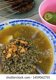 Lontong Kupang, Indonesia traditional food from East Java. It consists of young shell, shrimp paste or petis, and lontong. it is also sprinkle with fried sliced garlic and splash of lime juice