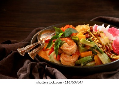 Lontong Medan. Popular Medanese  dish of rice cake with vegetable curry, shrimp with fermented soybeans, egg in red chili paste, vermicelli, potato crisps with anchovies peanuts, and crackers.