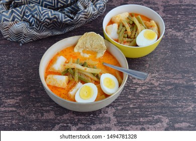 Lontong Sayur, Indonesian cuisine. Compressed rice cake or lontong with vegetables (chayote and yard long beans) cooked in coconut milk and spices. Served with boiled egg and emping cracker