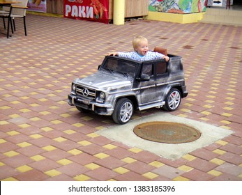 Loo (Sochi), Russia, 08.31.2017: A little blond boy rides an electric car for the first time and gives a bunch of different emotions - editorial photo