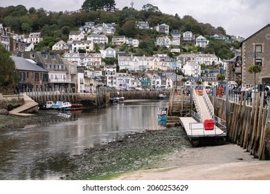 Looe, Cornwall, England UK - 10.06.2021: Houses rising above the river at Looe. A working fishing harbour popular with visitors.