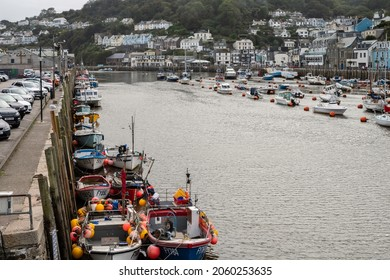 Looe, Cornwall, England UK - 10.06.2021: Fishing boats moored along the harbour wall, a working harbour popular with visitors.