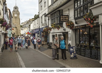 Looe, Cornwall, England, UK - September 15th, 2016. Tourists and locals in side street at Looe in Cornwall, England, UK with floral displays above shops and clock tower in the background.