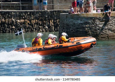 Looe, Cornwall / UK - August 05 2018: RNLI crew on a call out at the height of the holiday season.