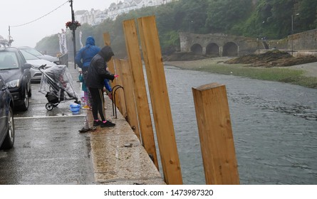Looe, Cornwall, UK. August 8 2019. Family on holiday still enjoying themselves crab fishing from the quay side at Looe, Cornwalldespite the heavy rain and wind.