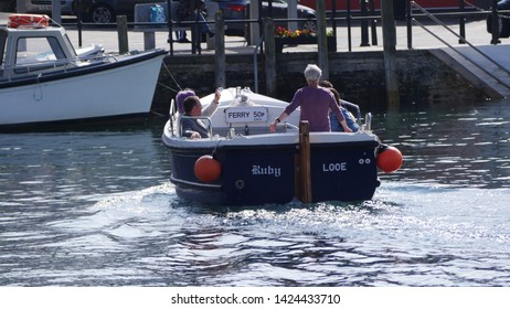 Looe, Cornwall, UK. June 14, 2019 West to East Looe ferry takes passengers across the Looe river on a warm sunny day