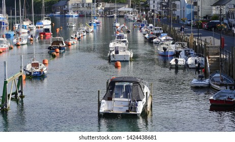 Looe, Cornwall, UK. June, 14, 2019. Views looking seaward along the Looe river on a sunny June afternoon, with fishing boats and pleasure boats moored at high tide