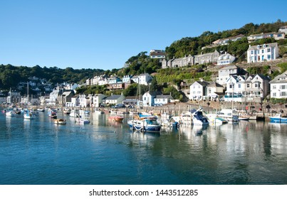 Looe, Cornwall, UK - September 26, 2010: View of harbour with boats and homes  on a sunny summer day.