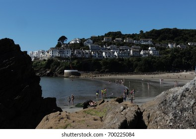 Looe, Cornwall - a view of tourists on the beach beneath a blue sky, with the banjo pier and West Looe in the background