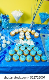 Look from above at delicious cupcakes standing on blue candy bar