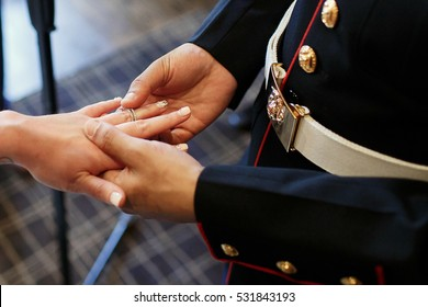 Look from above at groom in military uniform putting ring on bride's finger