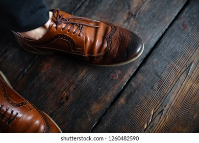Look from above at man in brown leather shoes standing on the wooden floor