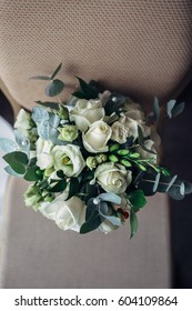 Look from above at tender wedding bouquet made of white roses and rose buds
