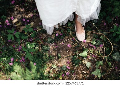 Look from above at woman in white dress walking on the ground in forest