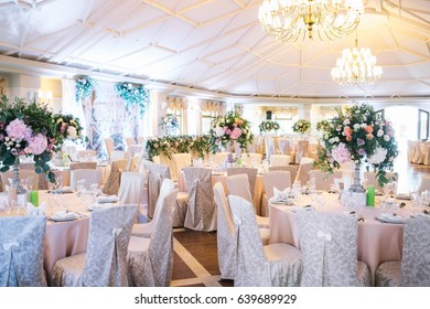 Look from afar at dinner hall decorated with beige cloth and large bouquets