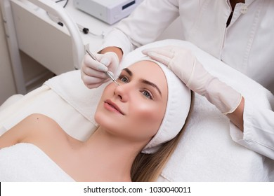 Look after your youth! Blackhead cleansing on woman face during facial treatment at beauty clinic. Young lady being done acne treatment with a help of mechanical instrument.