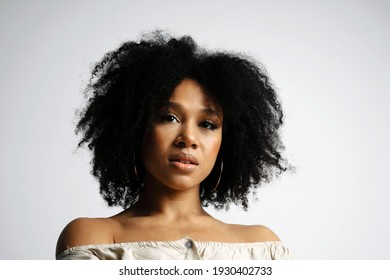 Look ahead. Beautiful clean smooth skin of the face. Black healthy curly hair. Young female model of afro appearance. Photo shoot in a photo studio on a white background.