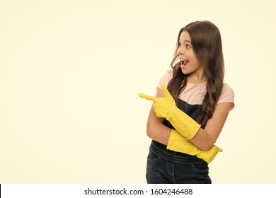 Look at all this mess. Girl yellow rubber protective gloves ready for cleaning pointing at copy space. Household duties. Girl cute kid cleaning around. Protect sensitive skin. Kid cleaning at home.
