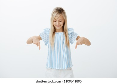 Look, it is amazing. Pleased curious smart little girl with blond hair, pointing and looking down, smiling broadly, feeling interested while looking downstairs and talking with mom who cooking dinner