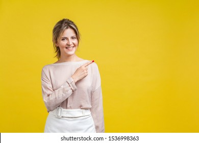 Look attention, advertise here! Portrait of joyous beautiful woman with fair hair in casual blouse standing, pointing aside and looking at camera. indoor studio shot isolated on yellow background
