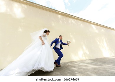 Look from behind at bride holding her dress while she and groom run along beige wall