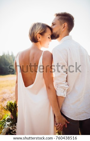 c35b4511d Look from behind at cheerful wedding couple kissing in the rays of evening  sun on the