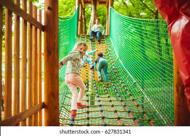 Look from behind at children climbing up the net