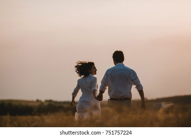 Look from behind at a couple holding their hands together while they walk across the field