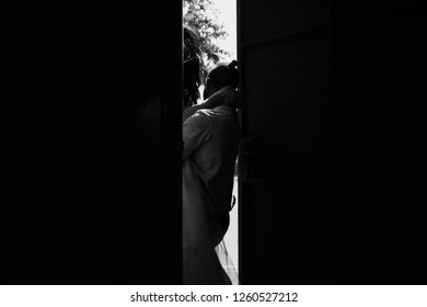 Look from behind the door at groom holding bride on his arms