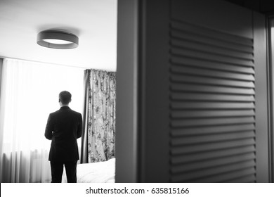 Look from behind the door at thoughtful man standing before the window