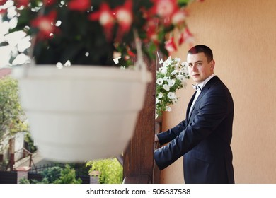 Look from behind the flowerpot at handsome man standing on the porch