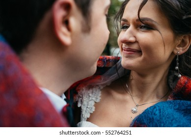 Look from behind groom's shoulder at curly bride admiring him
