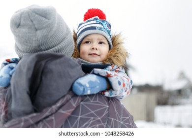Look from behind at little boy hugging father's neck