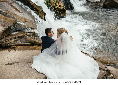 Look from behind at wedding couple sitting on the stones before a waterfall
