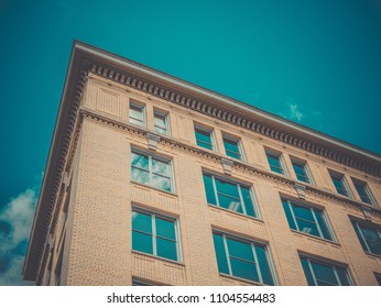 Look up beige building with pure blue sky and reelected sky in windows