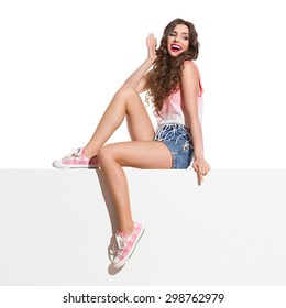 Look Below Me. Laughing young woman in pink top, jeans shorts and pink sneakers sitting on the white banner and pointing down. Full length studio shot isolated on white.