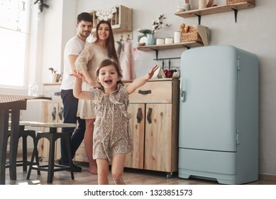 Look, it's cameramen there. Playful female child have fun by running in the kitchen at daytime of front of her mother and father.
