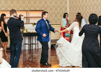 Look from the crowd at newlyweds dancing in the middle of wooden floor