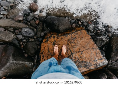 A look down to feet of a traveler standing on a stony beach just right before being splashed by approaching wave