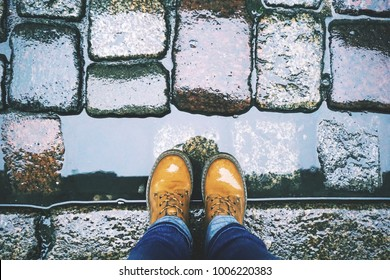 Look down at the feet in yellow shoes and blue jeans on the background of a wet old paving stone after the rain.