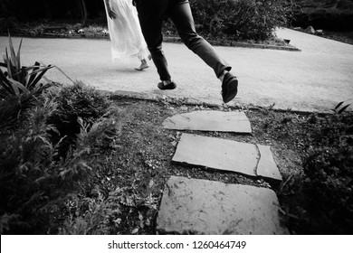 Look down at man and woman's feet running on the path in park