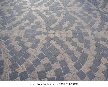 Look down at Thailand footpath tiles. - Cobble Eath tone stone arrange as wave.