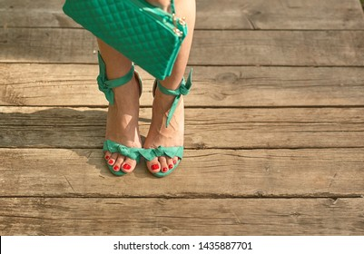 A look at the girl in retro sandals in heels and a handbag in her hand. Attractive legs of a girl in turquoise sandals with heels are filmed on a wooden bridge.