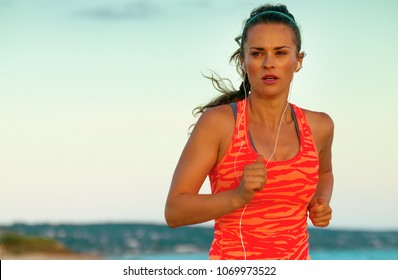 Look Good and feel great. fit active woman in sport style clothes on the beach in the evening jogging